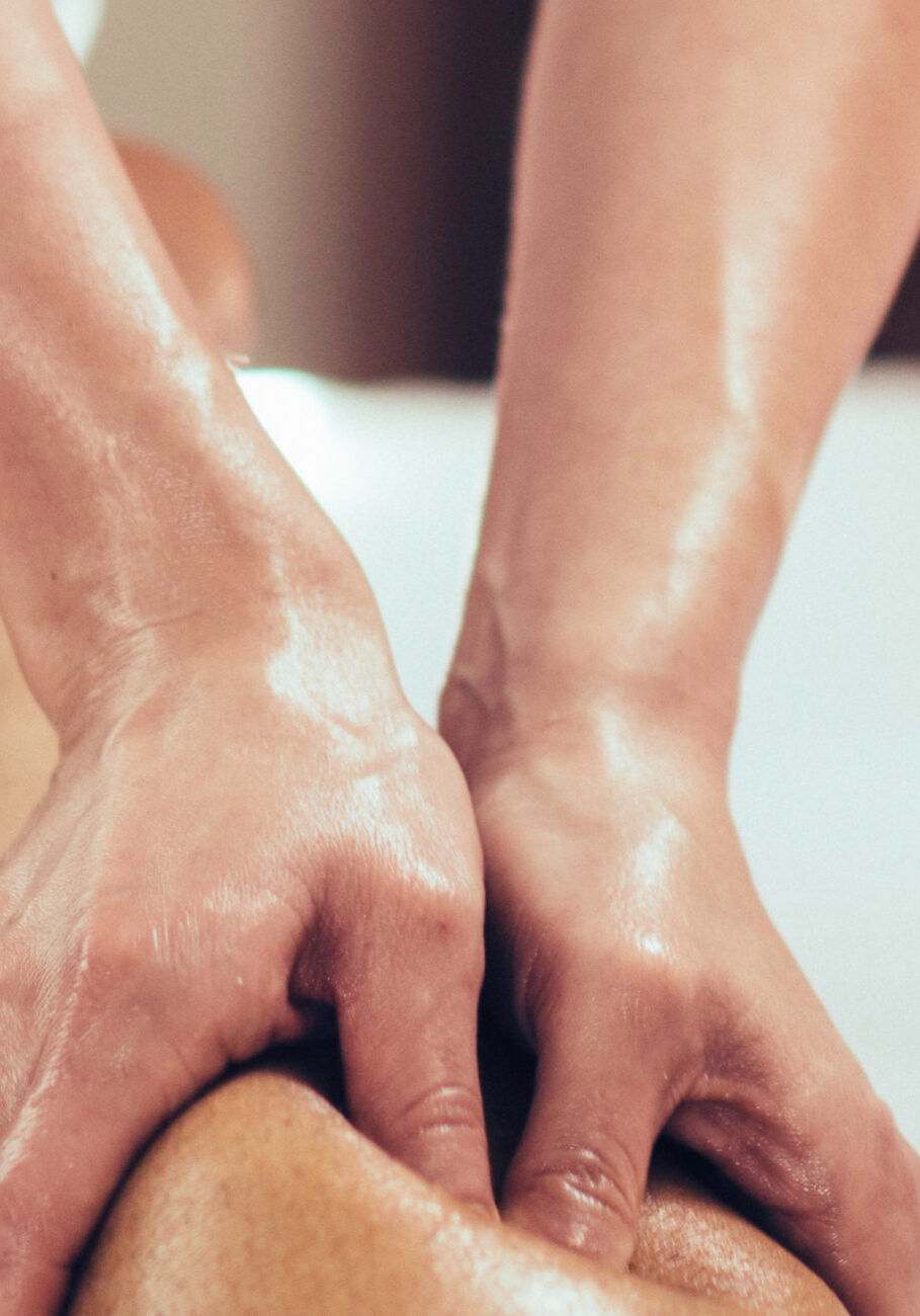 Physical therapyst massaging leg of male athelete